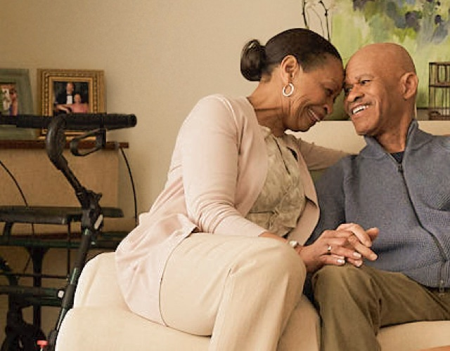 A post-stroke patient living with PBA and taking NUEDEXTA sits on a couch and shares a moment with his wife