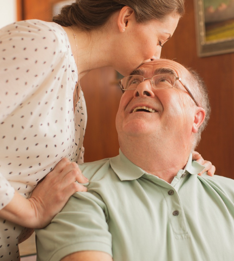 An Alzheimer's patient living with PBA and taking NUEDEXTA shares a tender moment with his daughter, who is his caregiver