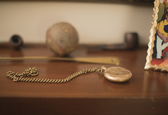 A pocket watch sits on a table with other mementos