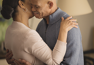 A post-stroke patient living with PBA and taking NUEDEXTA embraces his wife, who is his caregiver